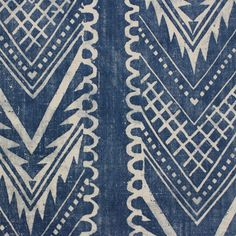 Vignatella Fabric A printed fabric with an inverted Aztec style chevron stripe in faded denim blue.