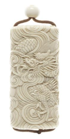 An ivory three-case inro century -- Of upright form, carved in relief with a spirited continuous scene of two dragons in dispute among swirling clouds, unsigned; with ivory bead ojime, unsigned. Art Japonais, Paperclay, Bone Carving, Objet D'art, Ivoire, Chinese Art, Chinoiserie, Japanese Art, Asian Art