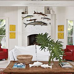 A school of fish are hung above a white painted fireplace while red leather chairs flank each side. A white cotton couch faces the fireplace.