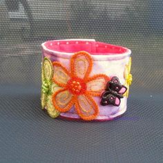 This fun bracelet is made from a purple tie dye felt and a pink polka dot felt on the back. It is decorated with a yellow, green and orange flower and beads and three colorful sparkly buttons.The bracelet measures 8.25 inches/21cm from snap to snap. And it is about 2 inches/ 4.5 cm wide.The snaps are nickle free.care: hand wash � by HandmadeFuzzy