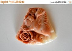 ~~~Please see announcement on shop home page for current information on deals, offers, and shipping.~~~ Hand carved stone pendant is a winged pig, or flying pig.  The color is a rusty orange, and off white..  The stone is natural Red Malachite, with no color enhancments.   I can't say enough how gorgeous this piece is, and what  suberb craftmanship is used to make this one of a kind stone pendant.  Pendant is drilled from front to back at the top of the pendant.    Measurement is 45x41x11mm…