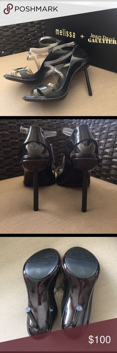 Melissa + Jean Paul Gaultier - Strappy Black Heel Stunning black Melissa jelly heels from their collab with French designer Jean Paul Gaultier. NEW IN BOX! Never worn . Original saks tag still on box retail $260. Also comes with original dust bag. Inside of box says April 3rd 2015 which I'm assuming is when they were manufactured :) Made of waterproof PVC with plastic upper. Size 6 US, 35 Brazil, 37 European. Made in Brazil. 4.25 inch spike metal heel. These were a little big for me I think…