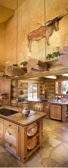 Pioneer Log Homes - The kitchen features two islands and a faux-painted plaster wall. - #WesternHome