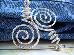 For a link, form a coil with a hammered open spiral on each end.  Connect with either jump rings or figure 8 links.
