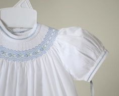 Adorable dress from Feltman Brothers' line Freidknit Creations. White batiste smocked bishop dress with lovely detailing. Finely detailed zig zag blue smocking with blue hand embroidered rosettes and