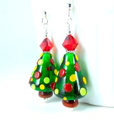 Handmade Christmas tree dangle earrings featuring bright green, red, lime green and yellow, SRA artisan crafted Christmas tree lampwork beads; sterling silver; and Light Siam Satin Swarovski crystals.  These adorable earrings are composed of beautiful 16mm lampwork beads created by an SRA lampwork artist. The beads are transparent bright green with polka dots of red, yellow and lime green. Light Siam Satin Swarovski crystals compliment the beads and add sparkle. Sterling silver beads, head…