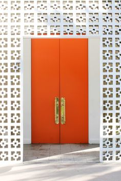 Vibrant orange doors at the entrance of The Parker Palm Springs