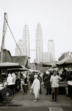 The Petronas Towers looming over the Malay area of Kampung Baru, Kuala Lumpur, Malaysia. Kampung Baru is a Malay enclave in the heart of Kuala Lumpur.