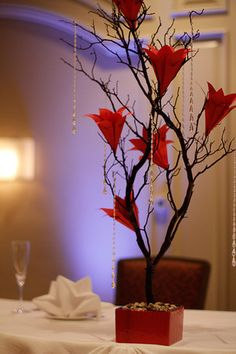 Manzanita Centerpieces With Red Origami Flowers. I'd rather have real flowers but like the box and the crystals hanging down.