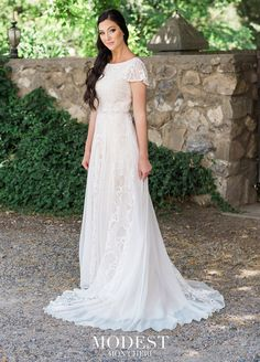 b75554b3831e Mon Cheri Modest is Boho-chic with a feminine twist. This soft allover lace  A-line modest wedding gown has fluttering short sleeves, a Sabrina  neckline, ...