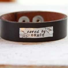 "Chocolate espresso leather, 3/4"" wide, and 9"" in length... It has 2 steel snaps to adjust the length down a bit if needed. (this size will fit most medium to large women.)A silver plate is stamped with the words ""saved by grace"" along with our pretty leaves. It has hammered edges and is attached to it with rivets. Very rustic and chunky. Items ship within 2 weeks and come boxed, ready for gift giving.This necklace is a copyrighted TheRustedChain ori..."