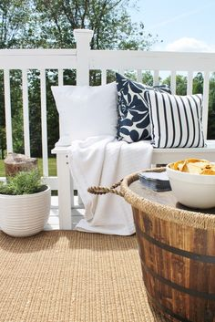 In this backyard makeover, City Farmhouse created a round coffee table by adding casters and a large tray to a large wood barrel planter. Viola, extra storage!
