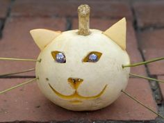 Halloween Pumpkin Decorating : Cat lovers will appreciate this white-pumpkin cat carving. Replicate cats' stunning eyes by inserting marbles in the eye cutouts, while stiff plant stems work perfectly as whiskers. With very little carving, this animal is a wonderful idea for pumpkin-carving beginners.