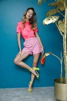 Playera tie dye rosa neón y short rosa chicle That's It, sandalias con textura de víbora amarillos neón Westies y clutch naranja con cadena beige Steve Madden.