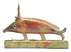 Egyptian Bronze Votive Oxyrhynchus Fish, Late Period - Ptolemaic,   664-30 BC It wears the crown of Hathor and uraeus. Its neck is engraved with a usekh collar and its eyes are inlayed with bronze and silver. These fish, the medjed, a species of elephantfish in the Nile river were believed to have eaten the penis of Osiris after his brother Set had dismembered and scattered the god's body. A settlement in Upper Egypt, Per-Medjed, was named after the fish,,,,,,