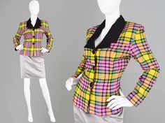 """An incredible vintage womens jacket from the 1980s in a vibrant multicolored check jacket. With a fitted silhouette and contrasting black lapels. The padded shoulders (which can easily be taken out) give an edgy, high fashion look. Size: fits roughly like a modern womens Small to Medium (Check measurements to ensure best fit) Bust - 38"""" / 96cm (Remember to leave a few inches room for movement and clothes underneath) Waist - 28"""" / 71cm Length (Shoulder to Hem) - 22"""" / 56cm Shoulder to…"""