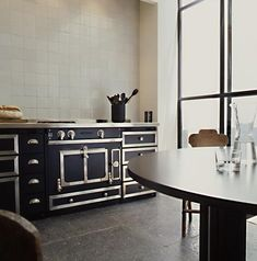 Antwerp-based architect Vincent Van Duysen has designed earthenware bowls for When Objects Work and cascading crystal chandeliers for Swarovski. We especially admire his kitchens; see more of his work at Vincent Van Duysen. Rustic Kitchen Cabinets, Kitchen Stove, Kitchen Dining, Open Kitchen, Dining Room, Home Decor Kitchen, Kitchen Interior, Black Kitchens, Home Kitchens