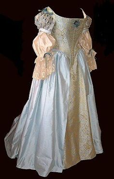 side profile of blue-gold 17th century dress with lace cuffs and ribbon detail