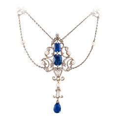 """Edwardian Pearl Sapphire Diamond Drop Necklace. This lovely festooned design highlights three fine sapphires displaying a very appealing shade of blue, together weighing approximately 5.50 carats, accompanied by ten small diamonds totaling approximately 0.25 carat, all punctuated and perfectly balanced by ten small round pearls, completed by a 16"""" long cable link chain. 2 1/2"""" long at center, platinum / 18 karat gold. Heirloom antique estate necklace circa 1910."""