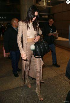 Kendall Jenner arrive à l'aéroport de LAX à Los Angeles, habillée d'un manteau, d'une legging et de sandales Balmain (collection printemps-été 2016), d'un crop top beige et d'un sac Givenchy (modèle Lucrezia). Le 19 novembre 2015.
