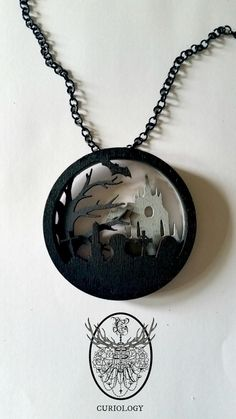 Our first release of layered silhouette necklaces, we have 3 others available on separate listings...Deep Blue, Midsummer Moon and Outbreak. Necropolis depicts a misty graveyard, with a church looming in the background, with a bare tree, flying bats, neglected headstones and graves.These 3 layer wooden pendants are designed, laser cut, and hand painted by us. They are unique, beautiful wearable art pieces. The pendant consists of 3 layers of laser cut wood, securely fixe...