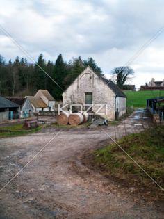 british farmhouse - A British farmhouse with round bails outside.