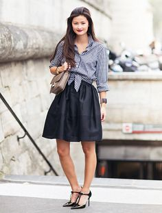 A gingham button-up is paired with a flared skirt and black patent leather heels.