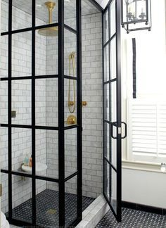 Amazing bathroom features a glass and steel shower walk in shower filled with white marble subway tiles on walls and ceiling accented with a gold rain shower head over a round shower shelf and black shower floor.