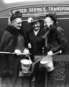 Three grandmothers from Hoxton, London, all over eighty, wait excitedly with their buckets and spades by the coach which will take them, and twenty two other Hoxton mothers, to the seaside at Littlehampton for the day, 16th July 1937.