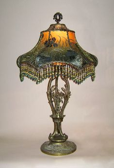 Wonderful antique Chinese chalkware base by artist E. Hunt is adorned with a exotic Napoleon lampshade with antique Chinese embroidery and vintage dogwood silk flowers. The colors go from dusty pink to green. Hand beaded fringe in matching tones. Lights up beautifully.