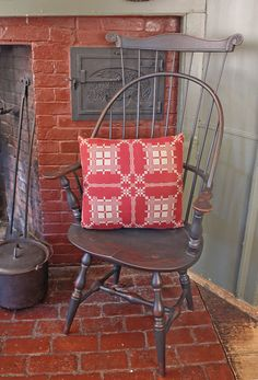 FARMHOUSE – INTERIOR – early american decor inside this vintage farmhouse seems perfect with this windsor chair set in front of an oversized fireplace.