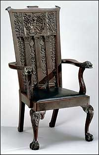 This Masonic chair was presented to the Williamsburg Lodge 6. Two inches thick and twenty wide, the back is solid mahogany, made in the shop of Anthony Hay.  Surmounted by a beautifully rendered cartouche and arms of the London Company of Masons, appropriately flanked by the rose of England and the thistle of Scotland, the classical orders of architecture stand out amid luxurious foliage, rosettes, and the age-old masons' tools of level, square, plumb, compass, and ruler.