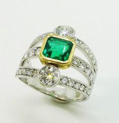 Lovely square emerald set in yellow gold with triple split shoulders to ring all set in 18 carat white gold.