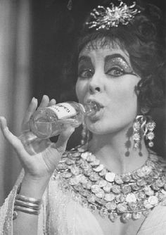 Liz Taylor on the set of Cleopatra wearing Joseff Hollywood Jewelry and drinking ???