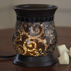 "Amaretto Swirl ScentGlow Warmer-Enjoy the Amaretto Swirl experience without the flame. Our electric warmer features a ceramic warming plate to diffuse the fragrance of Scent Plus® Melts or scented oil, sold separately. A hidden LED light sets the swirls of crushed glass aglow. Black cord. 6""h, 4¾""dia. $40.00 each"