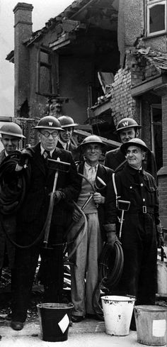 AIR RAID WARDENS 1940: Members of a team of Air Raid Wardens in a London suburb who have been tackling and extinguishing Luftwaffe incendiary bombs. The men are holding stirrup pumps, used to douse fires with water from a bucket.  Picture part of PA Second World War Collection : The Blitz