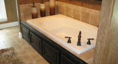 Bathtub shower. False cabinets at the bottom. White trim in bathroom. Custom tile around tub and shower wall.