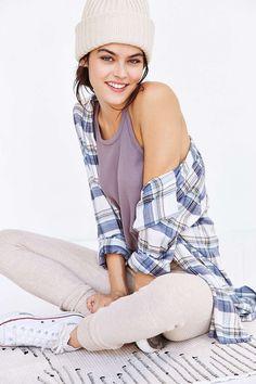 Neutral pants, purple shirt, plaid shirt, cream beanie, pink lip, white shoes