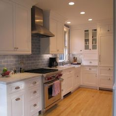 not sure about the light colored cabinets, but like the wood floors, white cabinets, stainless steel appliances, and touch of color idea