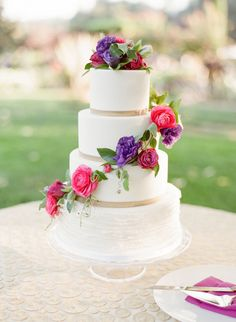 Bright pops of pink and purple make this wedding cake  a real statement piece.