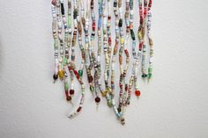 Beaded curtain from paper beads.  Same site (Trashy Crafter) shows another beaded curtain made by wrapping paper strips around paperclips & hooking the clips together.