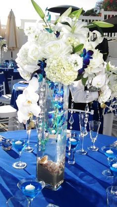 Sand Shells orchids color flowers- champagne glass floating candles- pretty centerpiece for coastal wedding