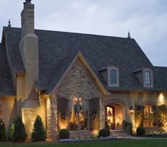 Architectural roof with curved detailing, mortar rub finish, copper gutters & lanterns, board & batten shutters and beautiful stack stone create a striking French Country exterior.   Hughes-Edwards Builders French Country Home - Charity Tour of Homes Nashville