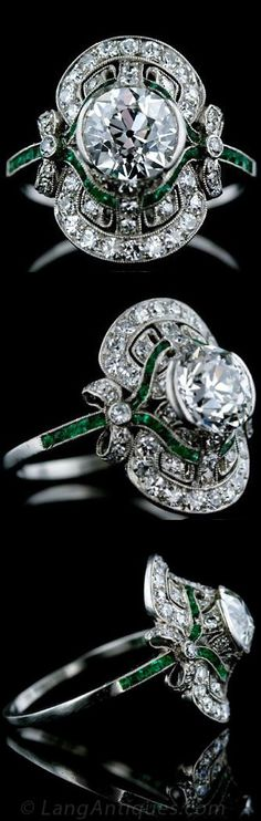 Late Edwardian Diamond Ring with calibrated Emeralds. This absolutely exquisite Edwardian diamond ring features a 1.80 carat sparkling European cut diamond set in a semi-bezel surrounded by small accent diamonds and calibre cut emeralds with adorable bow motif shoulders. Pristine Condition. #EmeraldRing