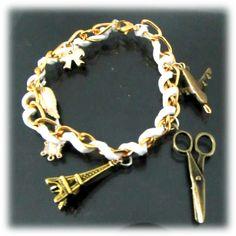 Pulsera de cadena dorada con cuero blanco y dijes.