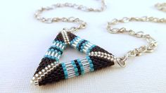 A beautiful 3d peyote triangle pendant! Made with Japanese delica beads in turquoise, silver lined crystal and black & Japanese bugle beads in silver lined crystal.    The sides of the triangle are approximately 1.1\/2(4 cm) long. It hangs from a cable chain necklace, the entire necklace is 28 (71cm) long. Just leave a note upon checkout if you would like the size adjusted. Check out my other beaded pendants and necklaces in many different colors, styles and designs…