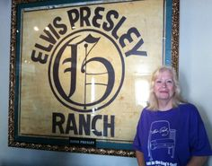 Donna Lewis with sign from Elvis ranch where her father worked. It's now located inside Hard Rock Cafe in Memphis.  Circle G Ranch