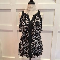 White House Black Market Medallion top Black halter top with multi tiered Ruffles all around. Has a touch of beige in it. Can dress this up beautifully with a black skirt or dress slacks. White House Black Market Tops Camisoles