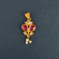 """An Indian 24K yellow gold ruby and diamond flower pendant, set with 6 rose cut diamonds weighing approx. 0.50CT and 2 facet cut rubies weighing approx. 1 CT as flower pedals. Three small peals dangle from the bottom of the pendant. The back of the pendant is decorated with a white and green filigree enamel. The pendant is 1 1/2"""" in length and weighs 3.0DWT."""
