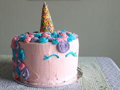 einhorn torte anleitung   hier ist ein pinkes einhorn mit einem großen bunten horn und mit einer mähne aus sahne und mit pinken, blauen und lila rosen